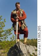 Купить «Викинг с мечом стоит на скале», фото № 13065265, снято 23 сентября 2015 г. (c) Дмитрий Черевко / Фотобанк Лори