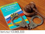 Купить «Уголовный кодекс, судейский молоток и наручники лежат на столе», фото № 13065333, снято 30 октября 2015 г. (c) Денис Ларкин / Фотобанк Лори