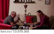 Купить «Мужчина и женщина курят кальян и играют в карты», видеоролик № 13079365, снято 19 ноября 2015 г. (c) Валентин Беспалов / Фотобанк Лори