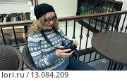 Модная женщина хипстер сидит в торговом центре и рассматривает фото в фотоаппарате. Стоковое видео, видеограф Земсков Андрей  Владимирович / Фотобанк Лори