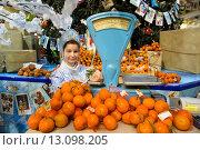 Купить «Продажа мандаринов на фоне новогодней елки в ГУМе города Москвы, Россия», фото № 13098205, снято 21 ноября 2015 г. (c) Николай Винокуров / Фотобанк Лори