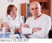 Семейный разговор. Злой взрослый мужчина сидит обидевшись, пожилая женщина смотрит на сына. Стоковое фото, фотограф Оксана Лозинская / Фотобанк Лори