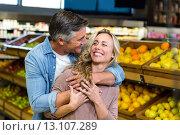 Купить «Smiling couple hugging in fruit aisle», фото № 13107289, снято 14 апреля 2015 г. (c) Wavebreak Media / Фотобанк Лори