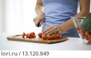 smiling young woman chopping tomatoes at home. Стоковое видео, видеограф Syda Productions / Фотобанк Лори