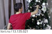 Купить «Мальчик подросток украшает елку», видеоролик № 13135021, снято 22 ноября 2015 г. (c) Валентин Беспалов / Фотобанк Лори