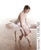 Балерина в белой пачке сидит на банкетке и завязывает пуанты.  Высокий ключ. Стоковое фото, фотограф Елена Троян / Фотобанк Лори