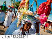 Купить «A Baiana woman carries a religious figurine during the ritual procession in honor to Yemanjá, the Candomblé goddess of the sea, in Amoreiras, Bahia, Brazil...», фото № 13332941, снято 24 октября 2018 г. (c) age Fotostock / Фотобанк Лори
