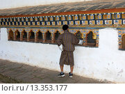 Junger Mann in traditioneller Kleidung an einer Gebetsmühle im Fruchtbarkeitstempel Chimi Lhakhang, Lobesa, Bhutan / Young Bhutanese man in traditional... Стоковое фото, фотограф Zoonar/Georg / age Fotostock / Фотобанк Лори