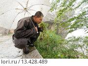 Купить «Shaolin Monk Shi De Jian examining vegetation at the San Huang Zhai Monastery on the Song Mountain, China», фото № 13428489, снято 28 сентября 2008 г. (c) age Fotostock / Фотобанк Лори