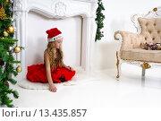 Грустная нарядная девочка сидит на полу в новогоднем интерьере. Стоковое фото, фотограф Максим Тимофеев / Фотобанк Лори