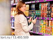 Купить «Woman shopping in the liquors section in supermarket.», фото № 13493509, снято 21 февраля 2020 г. (c) age Fotostock / Фотобанк Лори