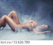 Beautiful nude young woman lying down surrounded with smoke. Стоковое фото, фотограф Oleksiy Maksymenko / age Fotostock / Фотобанк Лори