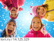 Купить «happy little children faces over blue sky and snow», фото № 14125329, снято 10 октября 2015 г. (c) Syda Productions / Фотобанк Лори