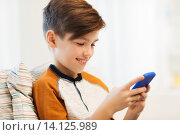 Купить «boy with smartphone texting or playing at home», фото № 14125989, снято 24 октября 2015 г. (c) Syda Productions / Фотобанк Лори