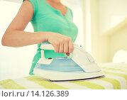 Купить «close up of happy woman with iron ironing at home», фото № 14126389, снято 25 января 2015 г. (c) Syda Productions / Фотобанк Лори