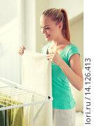 Купить «happy woman hanging clothes on dryer at home», фото № 14126413, снято 25 января 2015 г. (c) Syda Productions / Фотобанк Лори