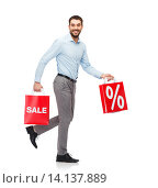 Купить «smiling man walking with red shopping bag», фото № 14137889, снято 3 октября 2015 г. (c) Syda Productions / Фотобанк Лори