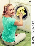 Купить «happy woman putting laundry into washer at home», фото № 14159469, снято 25 января 2015 г. (c) Syda Productions / Фотобанк Лори