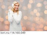 Купить «smiling young woman in winter earmuffs and sweater», фото № 14160049, снято 8 октября 2015 г. (c) Syda Productions / Фотобанк Лори