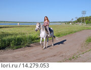 Купить «Счастливая девушка едет на белом коне по просёлочной дороге», фото № 14279053, снято 13 июня 2014 г. (c) Светлана Попова / Фотобанк Лори