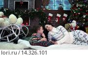 Купить «Мальчик с мамой лежат возле новогодней елки с мобильным телефоном», видеоролик № 14326101, снято 2 декабря 2015 г. (c) Сергей Мнацаканов / Фотобанк Лори