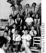 Chinese children singing in a choir. Chinese class learning communist patriotic songs. China, 1961. Редакционное фото, фотограф ARNOLDO MONDADORI EDITORE S.P. / age Fotostock / Фотобанк Лори
