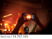 Купить «A fan among the concert crowd at up the Hammersmith Apollo in London is taking a picture with her smart phone at a J. Cole concert. UK 2013.», фото № 14707165, снято 22 июня 2018 г. (c) age Fotostock / Фотобанк Лори