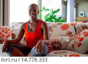 Купить «Young Woman Sitting on Sofa with Legs Crossed», фото № 14778333, снято 20 июля 2011 г. (c) age Fotostock / Фотобанк Лори