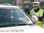 Купить «Сотрудник ДПС на службе беседует с водителем автомобиля. Городская улица», фото № 14782973, снято 5 октября 2013 г. (c) Михаил Михин / Фотобанк Лори
