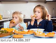 Купить «Children biting a dessert», фото № 14886397, снято 14 декабря 2018 г. (c) Яков Филимонов / Фотобанк Лори