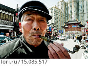 Купить «A man smoking in a traditional tobacco pipe (Chinese tobacco pipes are generally composed of three parts: a small bowl of metal (copper alloy), a stem...», фото № 15085517, снято 14 марта 2009 г. (c) age Fotostock / Фотобанк Лори