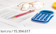 Купить «Бизнес-концепция. Таблица с цифрами, очки, калькулятор и ручка на столе», фото № 15304617, снято 14 октября 2015 г. (c) Валерия Потапова / Фотобанк Лори
