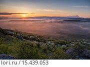 Купить «Лучи рассветного солнца пробивают туман у подножия горы», фото № 15439053, снято 2 мая 2015 г. (c) Матвей Солодовников / Фотобанк Лори