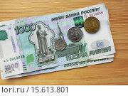Тысяча рублей и монеты, на деревянном фоне. Стоковое фото, фотограф Irina Ugorova / Фотобанк Лори