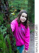 Купить «Young girl looking from behind a large tree in a temperate rain forest.», фото № 15647681, снято 10 ноября 2014 г. (c) age Fotostock / Фотобанк Лори