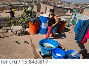 Купить «A Peruvian woman washes clothes in buckets outside a wooden house on the dusty hillside of Pachacútec, a desert suburb of Lima, Peru, 20 January 2015....», фото № 15843817, снято 20 января 2015 г. (c) age Fotostock / Фотобанк Лори