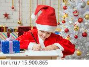 Купить «Девочка в костюме Санта-Клауса пишет список желаемых подарков на Рождество», фото № 15900865, снято 12 декабря 2015 г. (c) Иванов Алексей / Фотобанк Лори