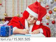 Купить «Девочка с энтузиазмом пишет поздравления в новогодней открытке», фото № 15901505, снято 12 декабря 2015 г. (c) Иванов Алексей / Фотобанк Лори
