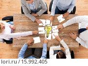 Купить «close up of business team with light bulb puzzle», фото № 15992405, снято 10 октября 2014 г. (c) Syda Productions / Фотобанк Лори