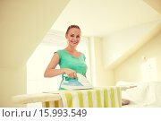 Купить «happy woman with iron and ironing board at home», фото № 15993549, снято 25 января 2015 г. (c) Syda Productions / Фотобанк Лори