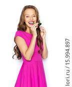Купить «happy young woman or teen girl with party horn», фото № 15994897, снято 31 октября 2015 г. (c) Syda Productions / Фотобанк Лори