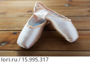 Купить «close up of pointe shoes on wooden floor», фото № 15995317, снято 15 октября 2015 г. (c) Syda Productions / Фотобанк Лори