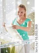 Купить «happy woman hanging clothes on dryer at home», фото № 16003969, снято 25 января 2015 г. (c) Syda Productions / Фотобанк Лори