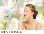 Купить «woman smelling perfume from wrist of her hand», фото № 16006361, снято 31 октября 2015 г. (c) Syda Productions / Фотобанк Лори