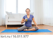 Купить «happy woman with smoothie sitting on mat at home», фото № 16011977, снято 13 ноября 2015 г. (c) Syda Productions / Фотобанк Лори