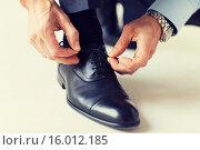 Купить «close up of man leg and hands tying shoe laces», фото № 16012185, снято 13 ноября 2014 г. (c) Syda Productions / Фотобанк Лори