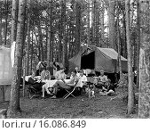 Купить «United States: c. 1925.A family enjoying all the comforts of home out in the woods, as they read, write, and play cards around the camp table.», фото № 16086849, снято 10 декабря 2019 г. (c) age Fotostock / Фотобанк Лори