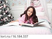 Маленькая девочка на кроватке читает книжку, рядом елка. Стоковое фото, фотограф Nataliya Pogodina / Фотобанк Лори