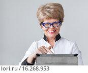 Довольная женщина пенсионер с улыбкой нажимает на тачскрин планшета. Стоковое фото, фотограф Кекяляйнен Андрей / Фотобанк Лори