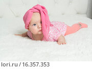 Маленькая девочка в платке на голове лежит на кровати. Стоковое фото, фотограф Алексей Чубов / Фотобанк Лори